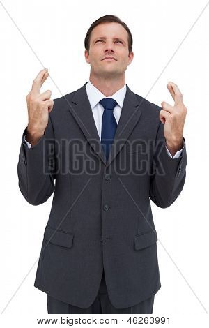 Serious businessman with fingers crossed is looking up on white background