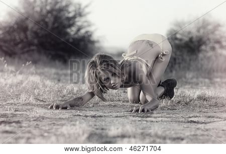 Fashion grunge bikini style.  Wild woman crouching in provocative pose in desert wilderness poster