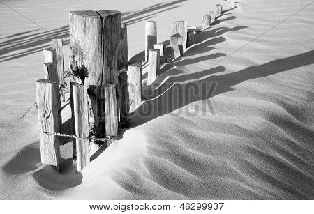 Black And White Image Of Wooden Fence In Sand Dunes