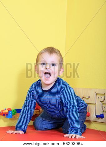 Cute caucasian toddler having fun in kindergarten.