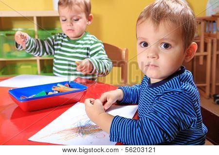 Cute european toddlers drawing a picture in kindergarten.