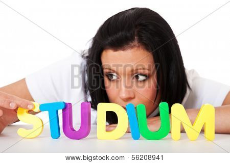 Young woman building the german term studium (eng. study) out of colorful letters.
