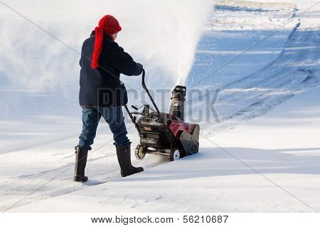 Senior Woman Clearing Drive With Snowblower