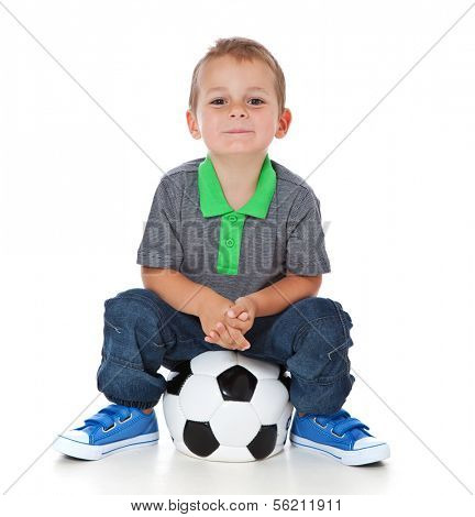 Attractive young boy sitting on soccer ball. All on white background.