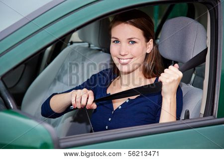 Attractive young woman in car fastens seat belt