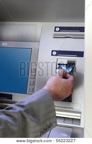man's hand inserting card into cash dispense