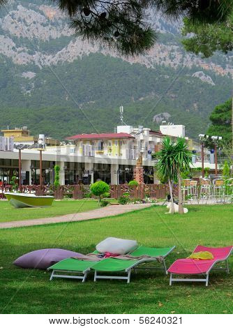 Sunbeds Are On The Green Lawn In Front Of The Hotel On The Background Of Mountains