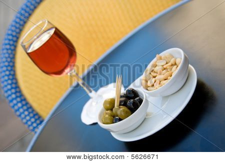 Parisian street cafe table with traditional French aperitif kir cassis and nibbles