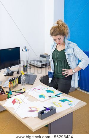 Creative designer standing behind her desk, overlooking various designs and concepts during for the materialization of a new product
