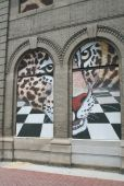 Three dimensional jaguar peering out of arched windows in an urban setting. poster