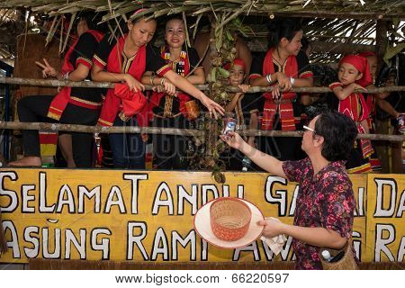 SARAWAK, MALAYSIA: JUNE 1, 2014: A lady passes a drink to Bidayuh tribe children taking part in a street parade to celebrate the Gawai Dayak festival. The Bidayuh is an indigenous Borneo native tribe.