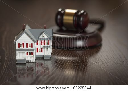Gavel and Small Model House on Wooden Table.