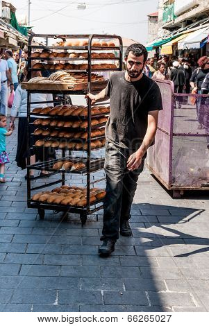 Worker With Trays Of Bread In Market In Jerusalem
