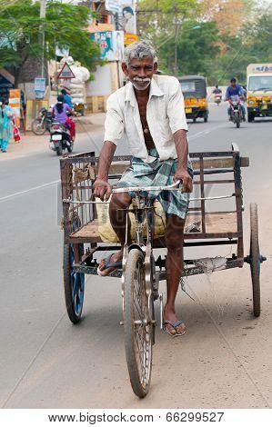 Indian man driving bicycle rickshaw at crowded city street