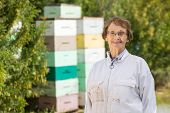Portrait of confident female beekeeper standing at apiary poster