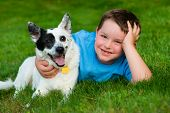 Child lovingly embraces his pet dog outdoors poster
