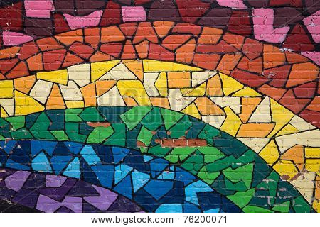 MONTREAL CANADA AUGUST 20 2014: Street art and graffiti. This rainbow mosaic is painted on a brick wall in the gay quarter of Montreal and signifies gay pride.