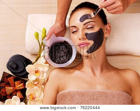 Cosmetologist smears cosmetic mask on the face of the woman in the sap salon