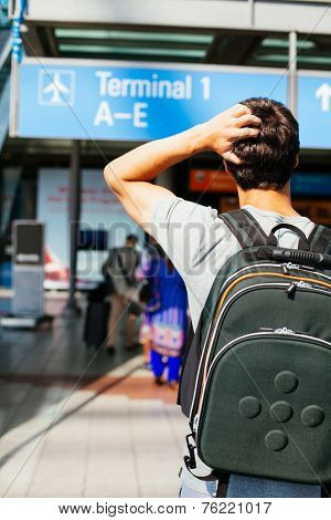 Confused young man with backpack looking for right direction in airport