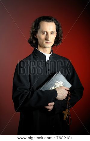 Conceptual Portrait Of Praying Priest With Wooden Cross And Holy Bible. Red Background