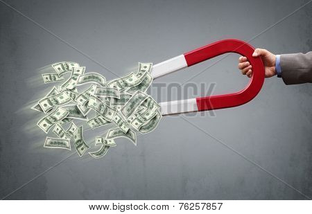 Businessman attracting money with a horseshoe magnet concept for business success, strategy or greed