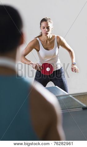 Attractive young woman playing table tennis indoors