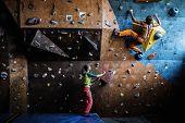 Muscular man practicing rock-climbing on a rock wall indoors  poster