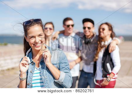 summer holidays and teenage concept - teenage girl in sunglasses and headphones hanging out with friends outside