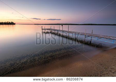 Sandy beach and dock beside lake at sunset. Minnesota, USA