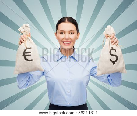 business, people, banking and finances concept - happy young businesswoman holding money bags with dollar and euro cash money over blue burst rays background