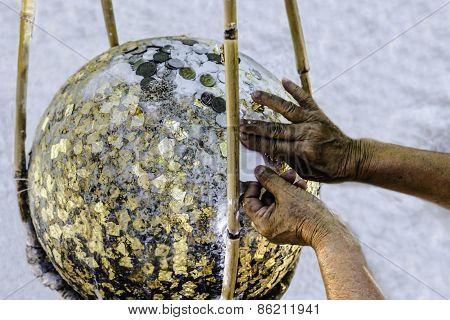 Hand Putting Gold Leaf On Boundary Stone
