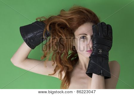 Woman covers her face with one hand with black glove