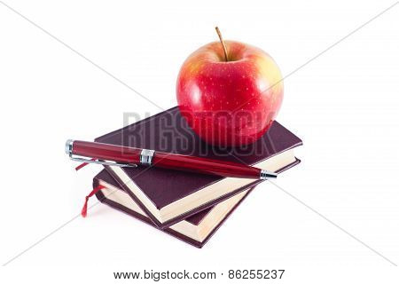 Apple On Stack Of Books With Pen