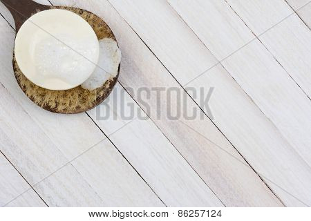 High angle shot of a sudsy bar of soap on a scrub brush. On a rustic wood surface the brush and soap are in the upper left corner of the frame leaving room for your copy.