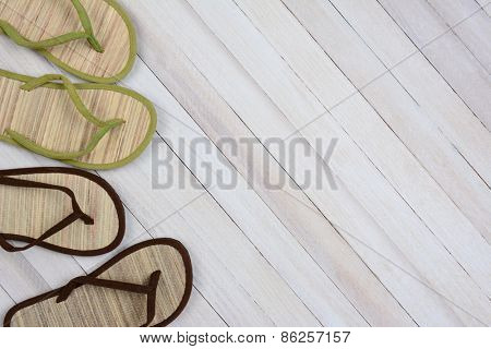 High angle shot of two pairs of flip flops on a wood background. Set to the left side of the frame leaving room for your copy.