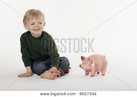 Young Boy and a Piggy Bank On The Floor