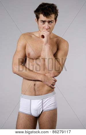Portrait of young adult handsome sleepy man naked muscular torso in white panties isolated on grey background