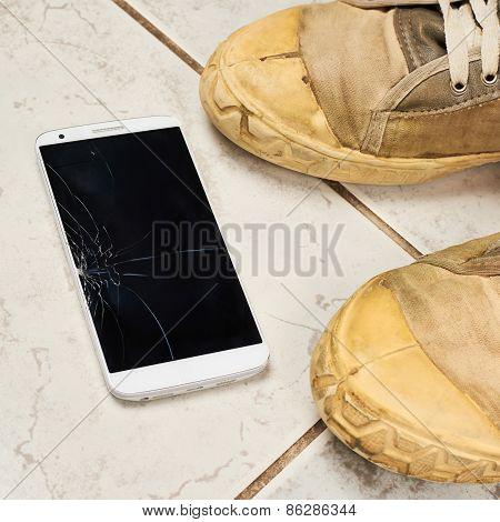 Broken smart phone over the tiles