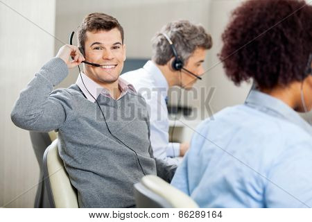 Portrait of young smiling male customer service representative using headset while colleagues working in office