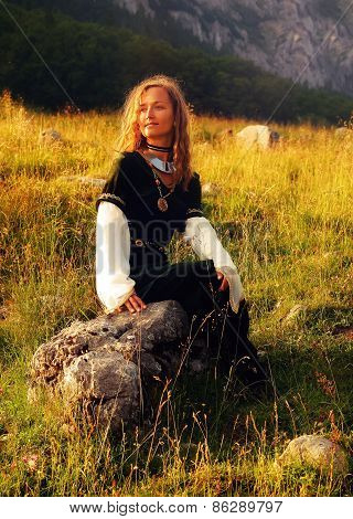 Mystical Medieval Maiden Sitting On A Wild Meadow Stone In A Mountain Landscape