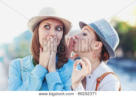 Young beautiful woman telling secret to her friend in the city outdoor poster