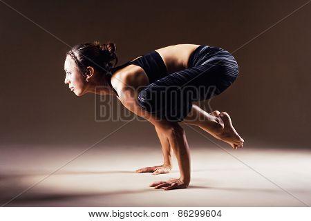 Beautiful sporty woman is doing yoga asana. Crane Pose. Bakasana. poster