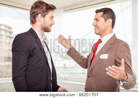 Cheerful young colleagues are greeting each other