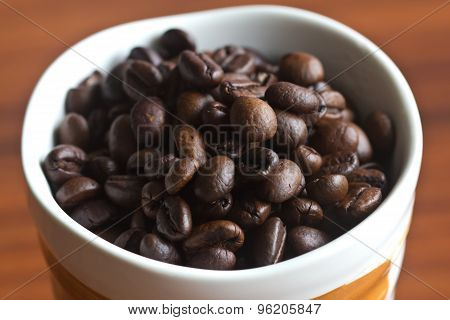 Coffee Beans In A Cup On A Wooden Table