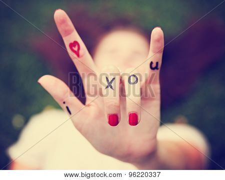 a young girl's hand with lettering i heart x o u written on it during summer making the rock on sign