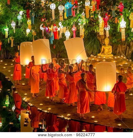 Chiang Mai, Thailand - November 6, 2014: Loy Kratong Festival, Buddhist monk fire candles to the Buddha and floating lamp on November 6, 2014 in Phan Tao Temple, Chiangmai, Thailand.