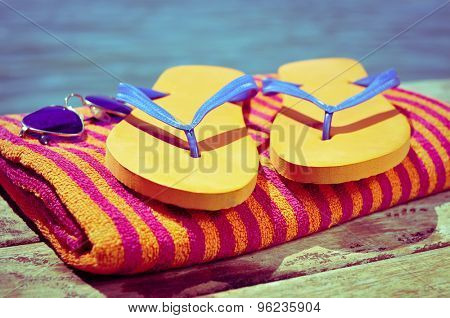 a pair of sunglasses, a pair of flip-flops and a beach towel, on a wooden boardwalk with the sea, a swimming pool or a lake in the background