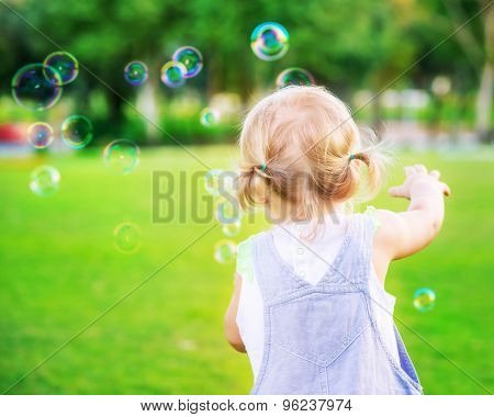 Little baby girl try to catch soap bubbles, having fun outdoors, playing games in the park, happy carefree childhood
