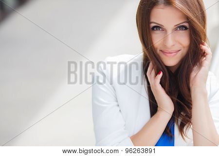 Portrait of attractive young girl in a Sunny summer day on the white terrace