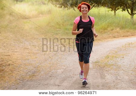 Athletic Adult Woman Jogging Along The Pathway